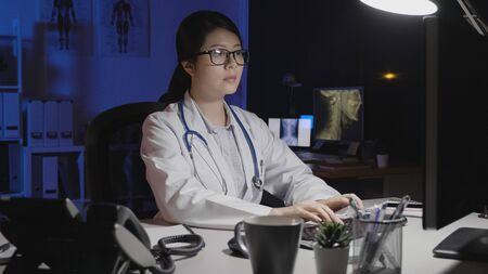 asian female doctor in dark clinic office typing on computer with eyeglasses serious face.