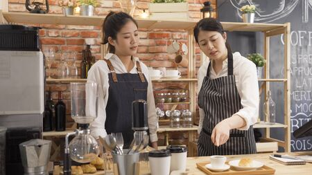 young girl new barista listening to colleague complaining her work