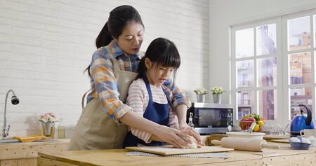 asian korean mother and daughter in apron using hands not rolling pin kneading dough for cookies together in kitchen on easter holidays. young mom teaching little girl baking cake on mothers day. Stock Photo