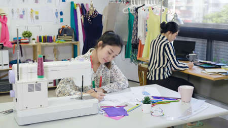 Two creative team fashion designers women drawing at sketches paper. skillful female dressmakers colleagues sitting at table brainstorming on new collection. ladies coworkers working in tailor shop. Stok Fotoğraf