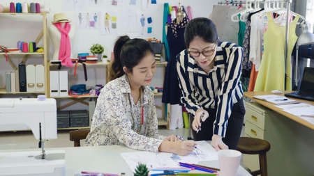 fashion design tailoring and people concept. team work of female designers drawing sketches at modern studio. young girl colleagues dressmakers discussing and talking on new collection in workshop.