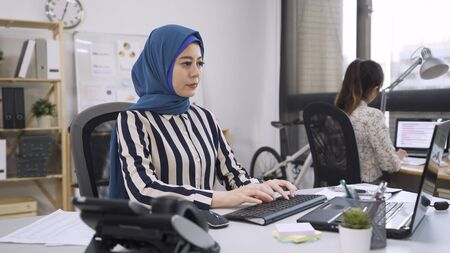 Successful multi ethnic team. Group of young business people working and communicating online typing on computer in creative office. asian chinese girl doing job islam female manager in headscarf. Standard-Bild