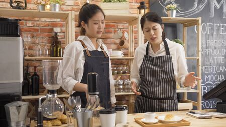 lady barista learning on first day on new job in cafe bar. angry young woman manager in restaurant scold at employee with make wrong order and telling to redo it again. waitress argue with boss