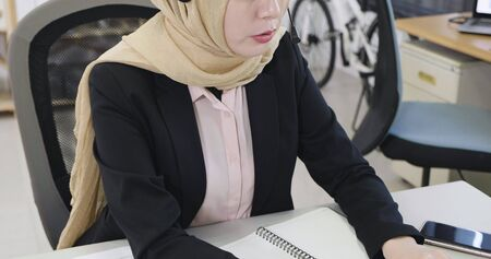 unrecognized muslim business woman wear headscarf hijab with headset talking phone call listening client complaining about product.