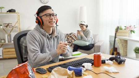 Young asian male gamer angry with bad team play video game on computer.
