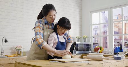 young elegant mom teaching girl kneading dough together for easter cake. family having fun baking