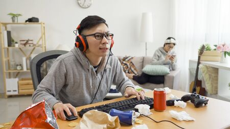 Attractive young asian guy wearing casual sitting at home playing online video game on computer.