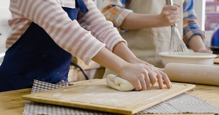 Little girl kneading flour with her mother whisking dough in bowl in background.