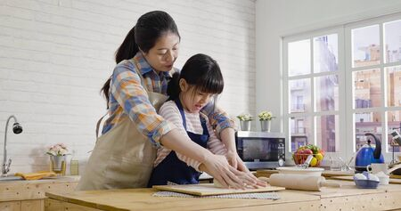 young beautiful asian chinese mom with cute little daughter making birthday cake for dad in day time at home. Stock Photo