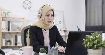 Young friendly arabic operator woman with headsets working in call center. 版權商用圖片