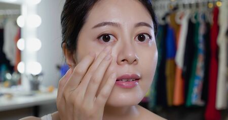 asian chinese woman model checking wrinkles around eyes and looking in camera as mirror. young girl examining her eyes bags after surgery of beauty therapy. attractive asian female smiling touch face Zdjęcie Seryjne