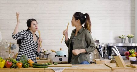 Two cheerful friends cook together and sing with spatulas as microphone.