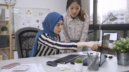 muslim female leader point finger at laptop screen asking japanese intern of mistake in project.