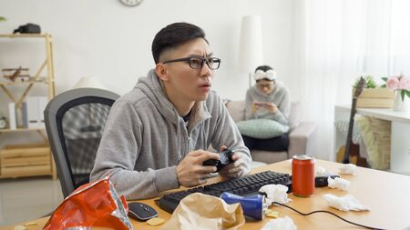 mama boy indoorsy relax at home on summer break with college girl friend playing online video game.
