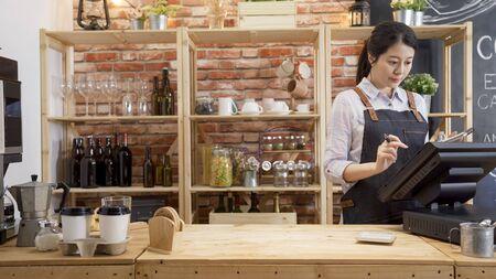 cameriera ragazza in grembiule utilizzando lo schermo commovente del dito del terminale POS nella caffetteria. Archivio Fotografico