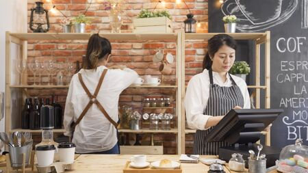 elegant young lady waitress hands touching tablet screen checking order. two girls staff working in modern cafe bar.
