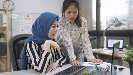 two confused asian trainee working online with laptop in difficult assignment at office. Reklamní fotografie