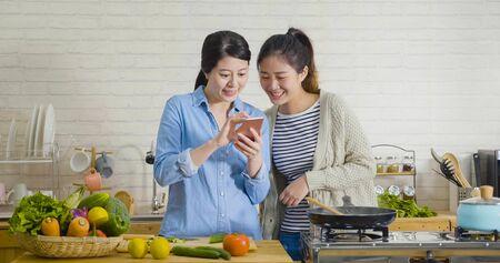 Zwei junge attraktive asiatische Mitbewohnerinnen kochen, während sie in der modernen Küche ein Smartphone gucken. Koreanische Damen, die während der Zubereitung des Frühstücks am Morgen ein Handy teilen und das Rezept im Internet betrachten.