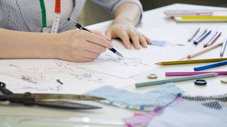 Talented dressmaker woman worker designing new dress on paper. young girl drawing on sketches with season unique fashion clothes in summer. close up hands working on desk in studio workshop.