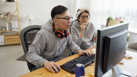 young asian couple sitting in messy home indoorsy homebody relationship. college student girlfriend and boyfriend playing online computer game together on pc screen eating chips snack on summer break