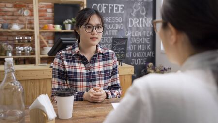Job interview candidate listen to recruiter in cafe shop. concentrated nervous asian woman applicant sitting at wooden table with hands holding together looking at hr manager in coffee bar indoors.