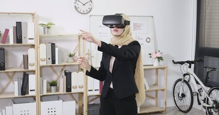 islam female manager in black suit and hijab using VR technologies. Confident young muslim woman in virtual reality headset pointing in air while standing at her working place in modern cozy office