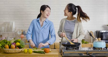 Young female friends in kitchen cooking together vegetarian meal. Preparing fruit salad healthy food in morning kitchen. happy asian women singing dancing and having fun while cutting and frying