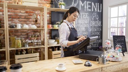 small business people and service concept. young asian girl waitress at wood bar counter in cafe store. woman bartender in apron using pos sale terminal machine to enter customer order from note.
