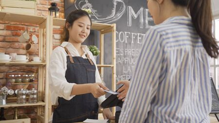 Customer paying for order with credit card in cafe. female bartender holding client's recharge card and returning it to female guest after payments on tablet in coffee shop. good service concept Banque d'images