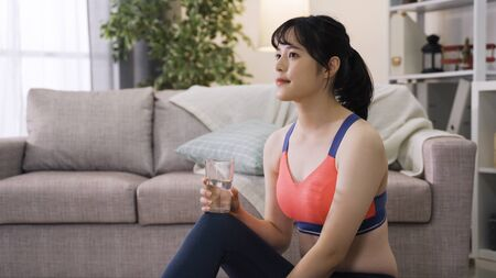 attractive asian girl in exercise outfit gulps down water and heaves a sigh of satisfaction. sportive chinese lady catches her breath and mops the sweat from her brow after workout. 版權商用圖片 - 147724871