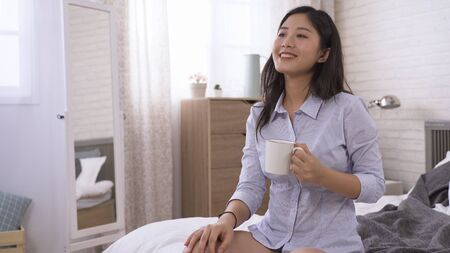 asian girl on diet is sitting in bedchamber and having green smoothie, looking happy. young woman touching her shirt, feeling hopeful that she can successfully lose some pounds with special drink.