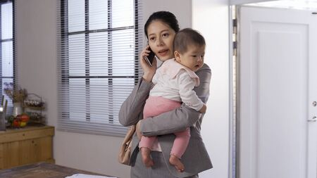 asian career woman arriving home with her baby is talking on phone. chinese businesswoman entering gate holding her daughter coping with work with smartphone. Banque d'images