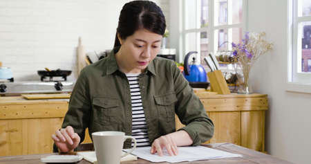 positive young woman make calculations on calculator with bills and document papers. lady check home expenses with cup of coffee in afternoon tea time. girl counting finance in kitchen interior.