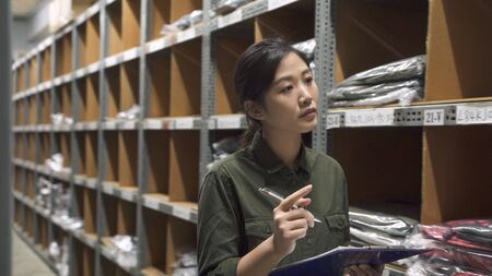manager woman doing stocktaking of products in cardboard box on shelves in warehouse using clipboard and pen. female professional assistant checking stock in factory depot. Physical inventory count.
