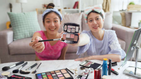 beauty blogger applying makeup in live streaming video face camera at home. focus view on make up cosmetic product with brush showing pink eyeshadow color. bokeh two girl internet influencer smile