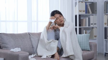 asian female patient staying at home with conoravirus covered in blanket and holding tissue is feeling chill and can't stop coughing. korean woman with infection touching sore throat and head hurts