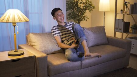 laid-back holiday asian guy changing tv channels found stand-up comedy and can't stop raising leg while laughing. korean male couch potato enjoying hilarious series at home alone before bedtime.