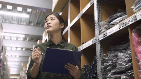 low to high portrait of warehouse worker woman looking up tall shelves doing inventory control in stockroom. female staff in uniform hold clipboard writing on paper while stock taking in storehouse