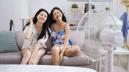 elegant cute ladies friends sitting close in sofa in comfort living room at home. beautiful female in shorts enjoy electric fan wind blowing hair smiling close eyes. girls feeling air cooler in house