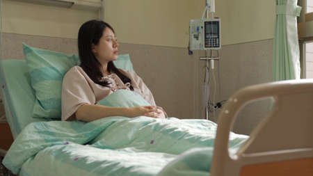 sick asian businesswoman is dealing with work on hospital bed on smartphone. chinese lady is checking phone message with solemn look. illness and hospitalization concept