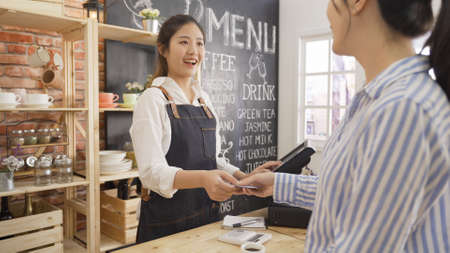 businesswoman customer at coffee shop pays smiling waitress with debit card. young girl barista using tablet while client doing payment on recharge card in cafe counter. happy small business owner.