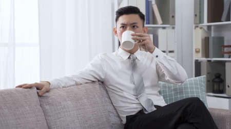 portrait male ceo is tapping on sofa with finger while pondering on marketing strategy. asian man drinking morning coffee and feeling concerned about the future.
