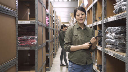 two asian chinese female factory coworkers checking goods on production shelves in warehouse. confident girl staff in uniform standing face camera smiling charming while working in stockroom.