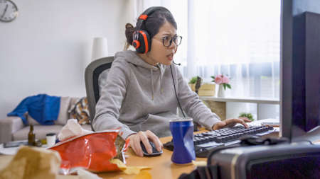 messy girl room. young college female student relax at home on summer break vacation. lazy asian japanese woman in glasses and headphones with microphone playing online computer game in bedroom.