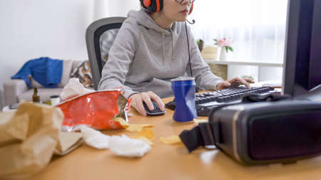 Messy bedroom table with beverage can and bags of snack. unrecognized young asian chinese lazy woman in dirty place wearing headphones and playing online video game. girl gamer using computer.