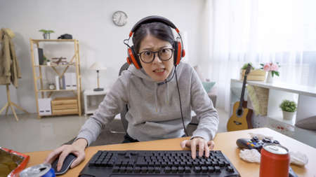 Funny young female gamer with headset playing video games on computer and looks at camera with astonishment. Portrait of surprised asian woman using computer in leisure time on summer break at home.