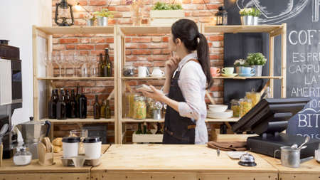 side view of young girl waitress in apron looking back on shelf finding tools of making coffee in counter. female barista searching for cup and thinking while holding note of customer order in cafe