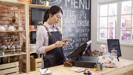 Young female bartender standing at bar counter counting money monthly salary for employee in cafe shop. woman business owner settle on cashbox money in closed coffee store after all day working.
