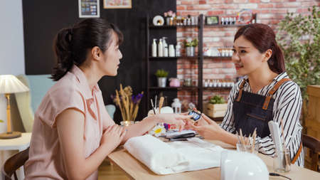 asian chinese manicurist making discussion with female customer before manicure in beauty salon. Master servicing girl client in studio with treatment on hands. woman point color on sample palette