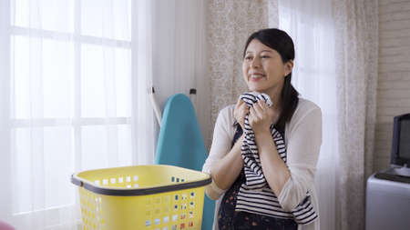 happy expectant mother standing by window in laundry room, smelling the clean and fresh shirt with satisfaction. woman face touching and feeling the soft and fragrant clothing. Banco de Imagens